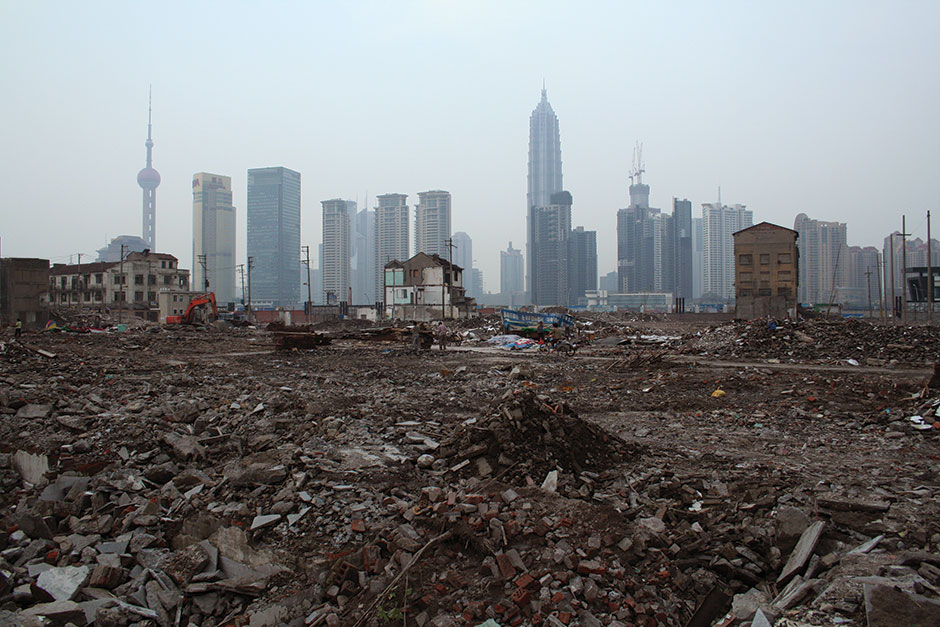 shanghai skyline behind a demolished neighborhood